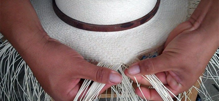 Hands weaving panama hat